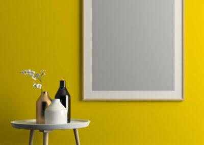 κίτρινός τοίχος με πολύ μεγάλη κορνίζα και τραπέζι με βάζα